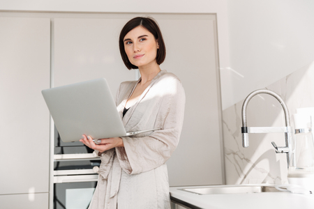 Portrait of caucasian adult woman wearing robe smiling and working or communicating online on white laptop in flat