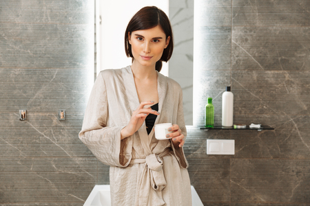 Photo of gorgeous woman 20s spending time in bathroom and caring for skin applying face cream