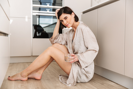 Caucasian gorgeous woman wearing robe sitting on floor in kitchen and drinking still fresh water from glass Stock Photo