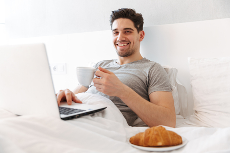 Photo of happy man in casual clothes having breakfast while lying in bed with laptop and cup of coffee