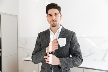 Portrait of handsome man in businesslike clothes looking on camera and holding cup of coffee on lunch time at home