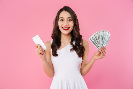 Adult asian woman in dress holding fan of dollar banknotes and smartphone in hands while looking on camera with smile isolated over pink background Фото со стока