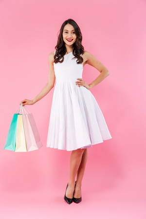 Portrait of a pretty young asian woman dressed in white dress holding shopping bags and looking at camera banknotes isolated over pink background Stock Photo