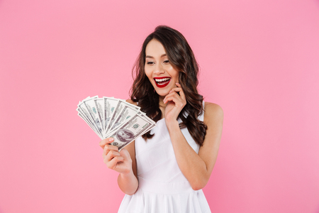 Image of happy rich asian woman smiling and looking on lots of money in dollar bills holding in hand isolated over pink background