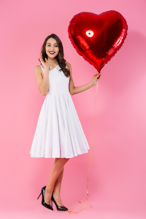 Full length portrait of a happy young asian woman dressed in white dress posing while holding heart shaped balloon isolated over pink background