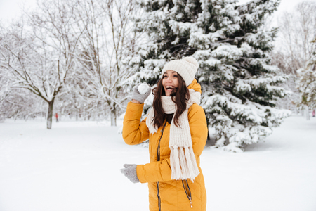 Playful young woman laughing and playing snowballs in park in winter