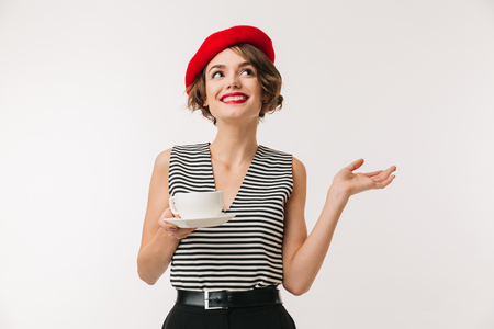 Portrait of elegant woman in striped shirt and red beret and holding cup of hot tea with hand aside isolated over white background Standard-Bild
