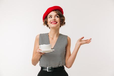Retrato de mujer elegante en camisa a rayas y boina roja y sosteniendo una taza de té caliente con la mano a un lado aislado sobre fondo blanco.