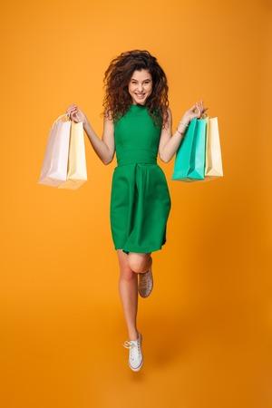 Beeld van gelukkige jonge vrouw status geïsoleerd over gele achtergrond. Kijkend naar camera bedrijf boodschappentassen.