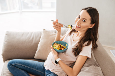 Pretty pregnant young woman having healthy breakfast while sitting on a couch Archivio Fotografico