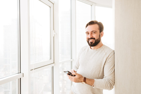 Photo of candid brunette guy 30s in white shirt, spending time near big window and holding mobile phone 免版税图像