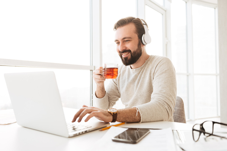 European joyous man 30s with short brown hair drinking tea and listening to music via wireless headphones while using notebook
