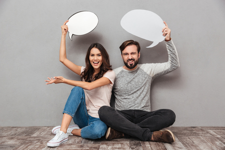 Photo of smiling handsome man with his wife sitting isolated over grey wall background. Looking camera holding speech bubbles. Stock Photo