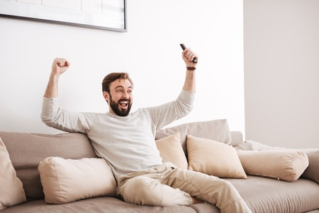 Portrait of an excited man holding remote control while sitting on a couch and watching TV 스톡 콘텐츠