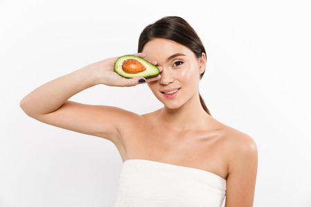 Happy asian brunette lady holding avocado near clean face and looking camera isolated over white