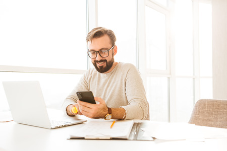Photo of attractive adult man 30s in casual clothing using smartphone while sitting at workplace