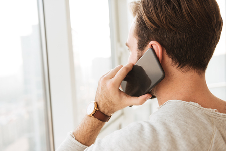 Closeup photo from back of man with short dark hair looking through window while having mobile call on black cell phone Stockfoto