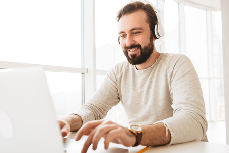 Photo of attractive mature man 30s in casual clothing typing text message or working on laptop while listening to music via earphones Stock Photo