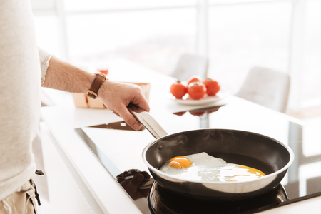 Cropped photo of caucasian bachelor in white shirt cooking omelet with vegetables in home kitchen using frying pan