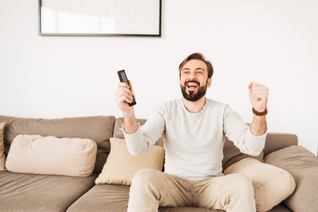 Excited cheerful guy having beard and mustache rejoicing win of football team while watching TV on sofa with remote control in hands Stock Photo