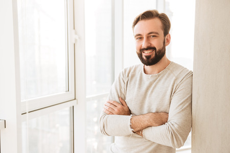 Portrait of smiling guy 30s having beard and mustache standing with hands crossed near big window in bright apartment