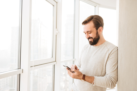Photo of relaxed guy 30s having beard and mustache spending time in flat and using mobile phone near big window