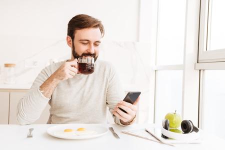 Hombre barbudo en camisa casual bebiendo té y usando un teléfono inteligente mientras come saludable con freír huevos en casa Foto de archivo