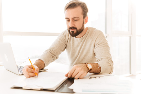 Image of smart adult man 30s in casual clothing writing notes on paper document while working in home office Stock Photo