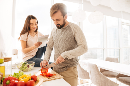 Portrait of a smiling young couple cooking salad together according to a recipe on a tablet computer