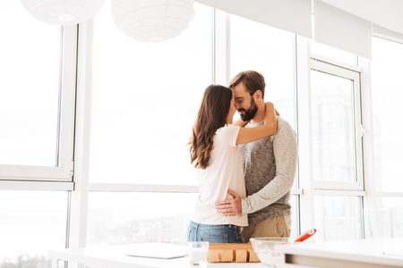 Happy young couple embracing while standing together near a window at home