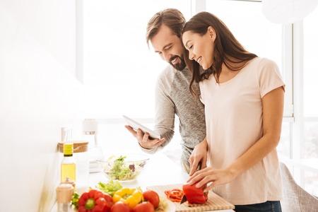 Portret van een vrolijke jonge paar kokende salade samen volgens een recept op een tabletcomputer