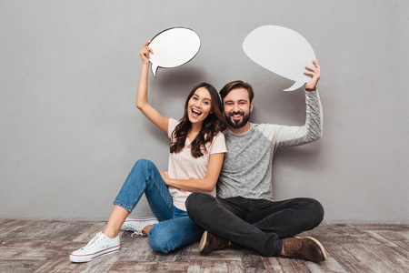 Photo of smiling handsome man with his wife sitting isolated over grey wall background. Looking camera holding speech bubbles. 版權商用圖片