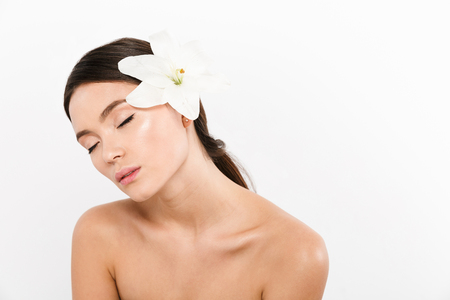 Young relaxed asian half-naked lady with closed eyes standing isolated with lily flower on shoulder