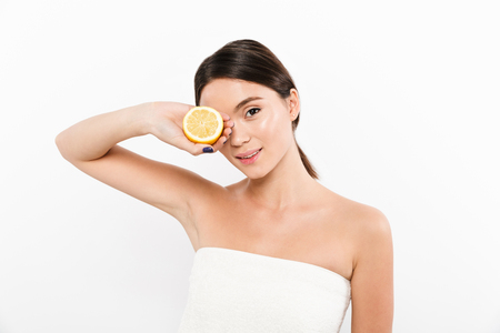 Young pleased asian woman in towel holding citrus near her face and looking camera isolated over white Stock fotó