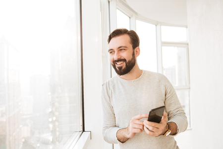 Communicative guy with in white shirt, looking through big window while chatting or typing text message on mobile phone