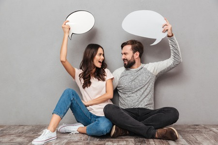 Image of confused man with his wife sitting isolated over grey wall background. Looking at each other holding speech bubbles.