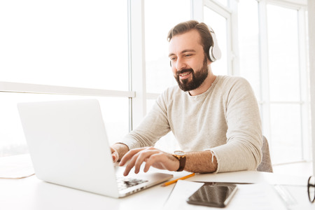 Positive european man with short brown hair chatting or scrolling social network on laptop while listening to music via headphones