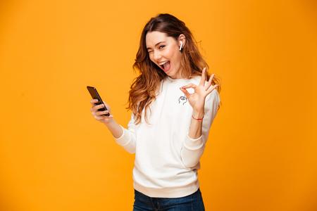 Mujer morena alegre en suéter con teléfono inteligente mientras muestra un signo bien y mira a la cámara con la boca abierta sobre fondo amarillo Foto de archivo