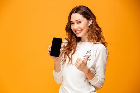 Obraz wesołej młodej kobiety stojącej na białym tle na żółtym tle słuchania muzyki pokazujący wyświetlacz telefonu komórkowego zrobić kciuki do góry.