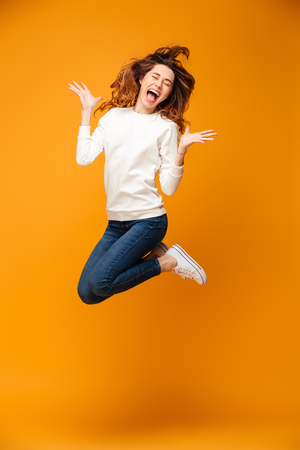 Full length image of Happy screaming brunette woman in sweater jumping and rejoices with closed eyes over yellow background