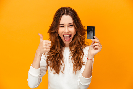 Cheerful brunette woman in sweater showing thumb up and holding credit card while winks and looking at the camera over yellow background