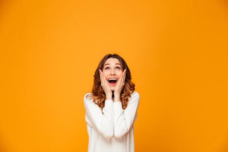 Mujer morena feliz sorprendida en suéter sosteniendo sus mejillas y mirando hacia arriba sobre fondo amarillo