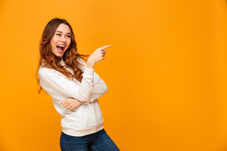 Cheerful brunette woman in sweater pointing away and looking at the camera over yellow background