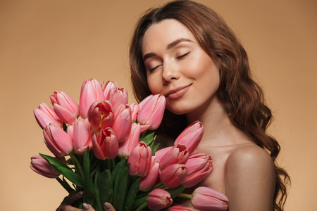 Nude attractive female 20s with natural makeup posing on camera with closed eyes while holding bunch of pink flowers isolated over beige background