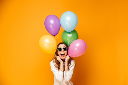 Surprised happy brunette woman in sweater and sunglasses holding balloons and looking at the camera over yellow background