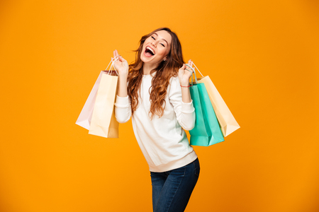 Cheerful brunette woman in sweater holding packages and looking at the camera over yellow background Stok Fotoğraf
