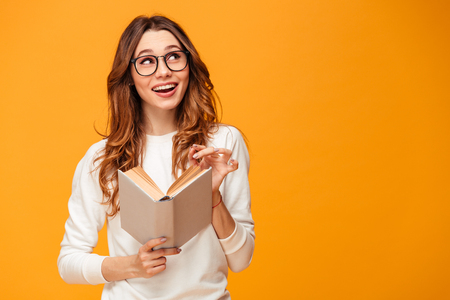 Pensive smiling brunette woman in sweater and eyeglasses holding book and looking up over yellow background