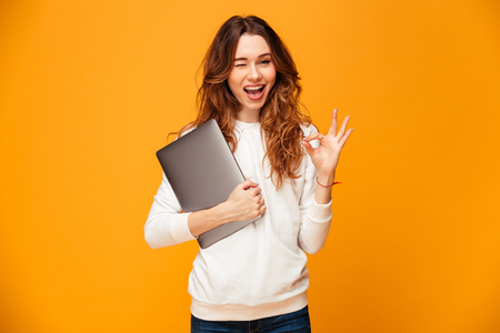 Image of cheerful young woman standing isolated over yellow background looking camera holding laptop computer showing ok gesture.