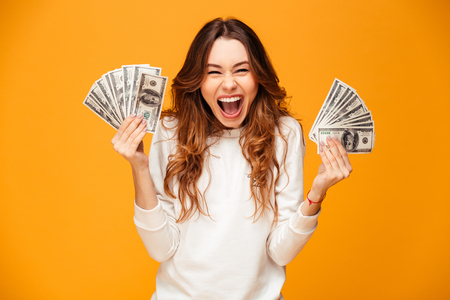 Happy screaming brunette woman in sweater holding money and rejoices while looking at the camera over yellow background