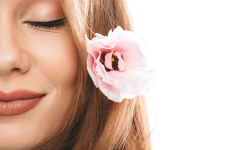 Half side closeup portrait of beautiful young woman 20s posing on camera with blossom lisianthus flowers in her long brown hair and closed eyes isolated over white background